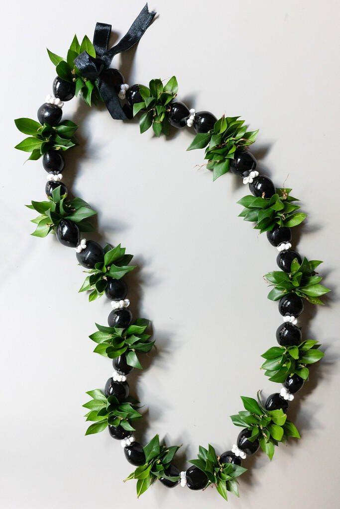 A lei made from kukui nuts and ti leaves