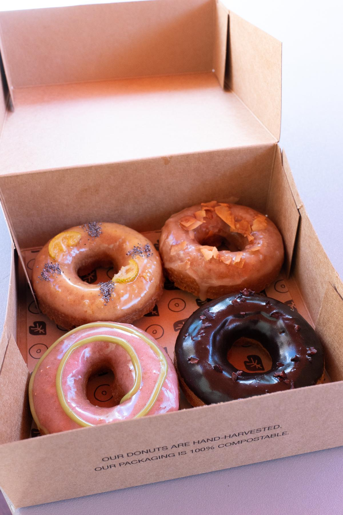 Opened box with four donuts from Holey Grail Donuts. The donut flavors are strawberry-green tea, Kauai chocolate and cacao nibs, maple and smoked coconut, and poppyseed and kumquats.