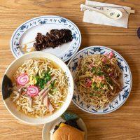 A table filled with food (saimin, fried saimin, teri cheeseburger, and teri sticks) from Shige's Saimin Stand.