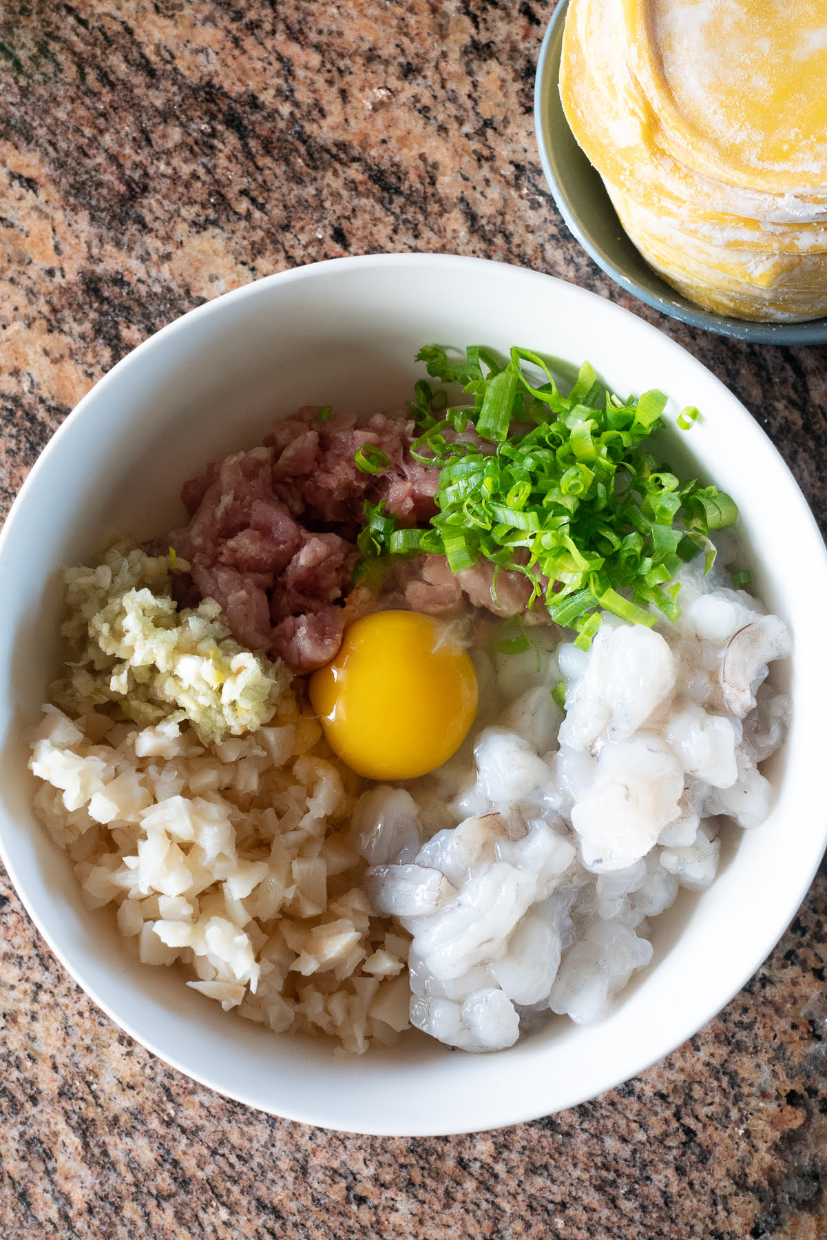 Mixing together ingredients for Pork Hash (ground pork, shrimp, egg, water chestnuts, green onions, garlic, cornstarch, soy sauce, oyster sauce, sesame oil, white pepper, and round dumpling skins).