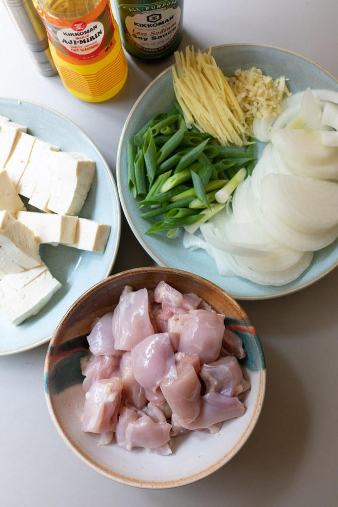All the ingredients for Chicken Tofu: chicken, tofu, onion, garlic, ginger, green onions, soy sauce, and mirin.