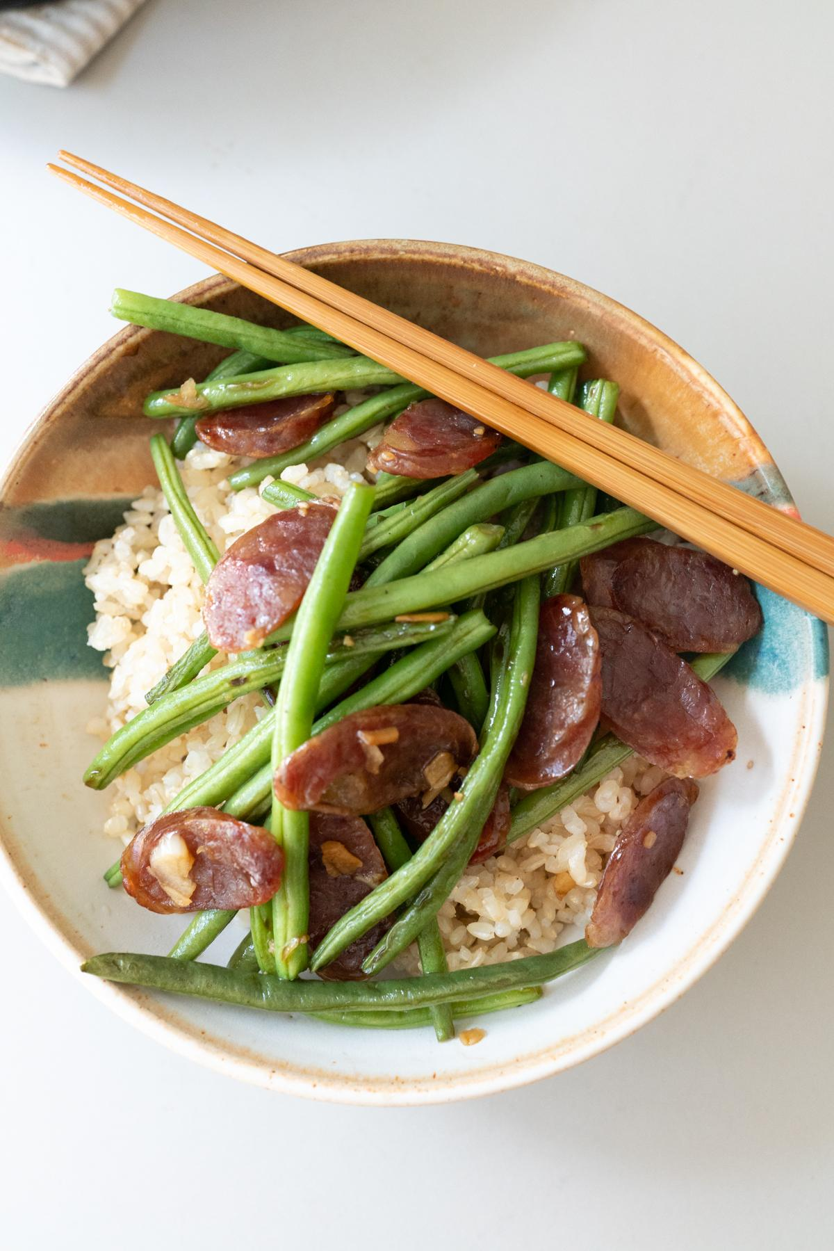 Chinese sausage and green beans served over rice in a bowl