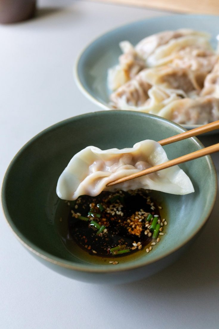kimchi dumplings ready to dip in the sauce and eat