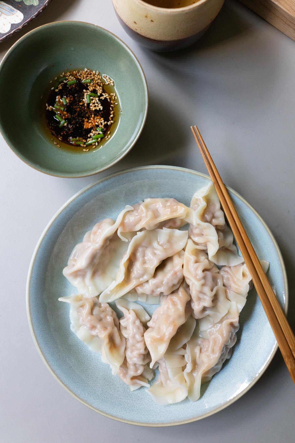 Plate of boiled kimchi dumplings and dipping sauce