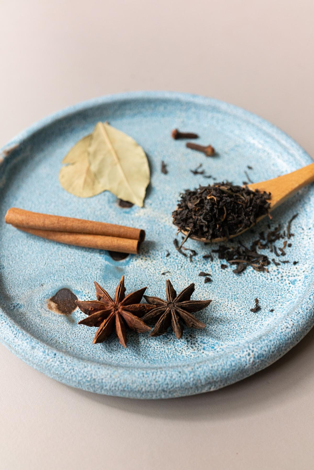 Spices for Chinese tea eggs. Clockwise from top: bay leaves, cloves, black tea, star anise, and cinnamon stick)
