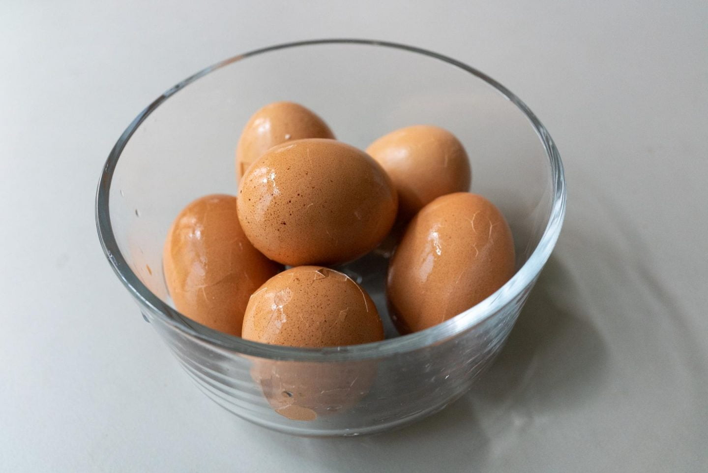 Gently cracking the shells of the boiled eggs before marinating