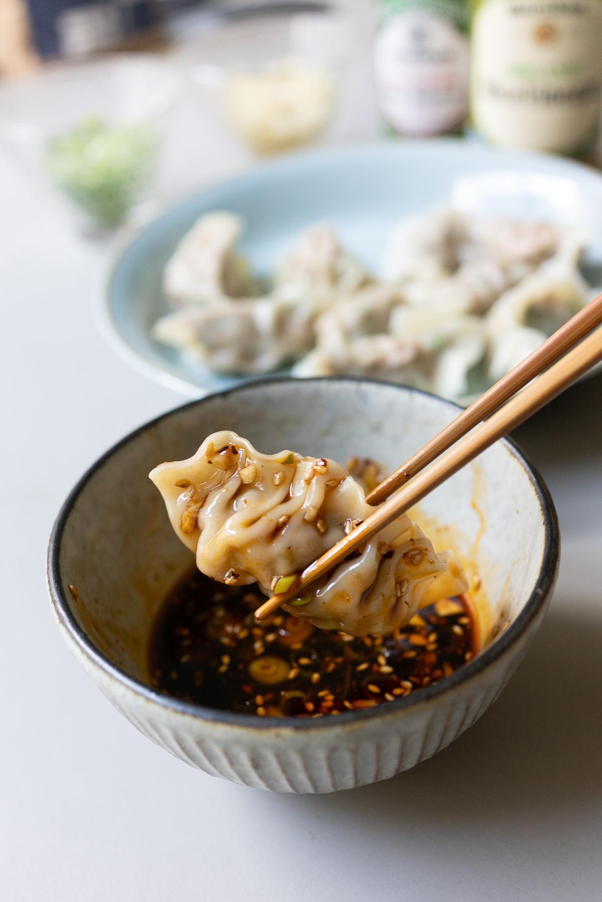 Dipping a dumpling in the Dumpling Dipping Sauce