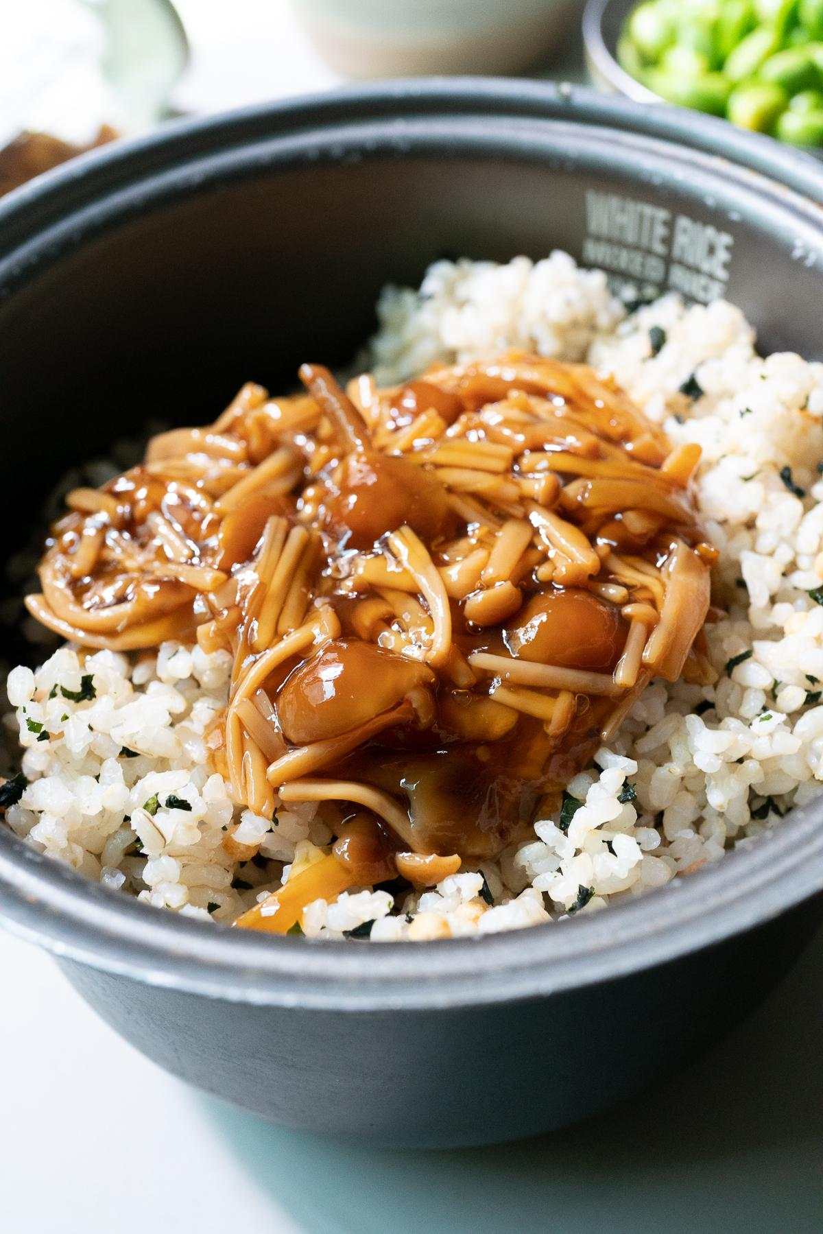 Pouring the Nametake (seasoned mushrooms) over cooked rice