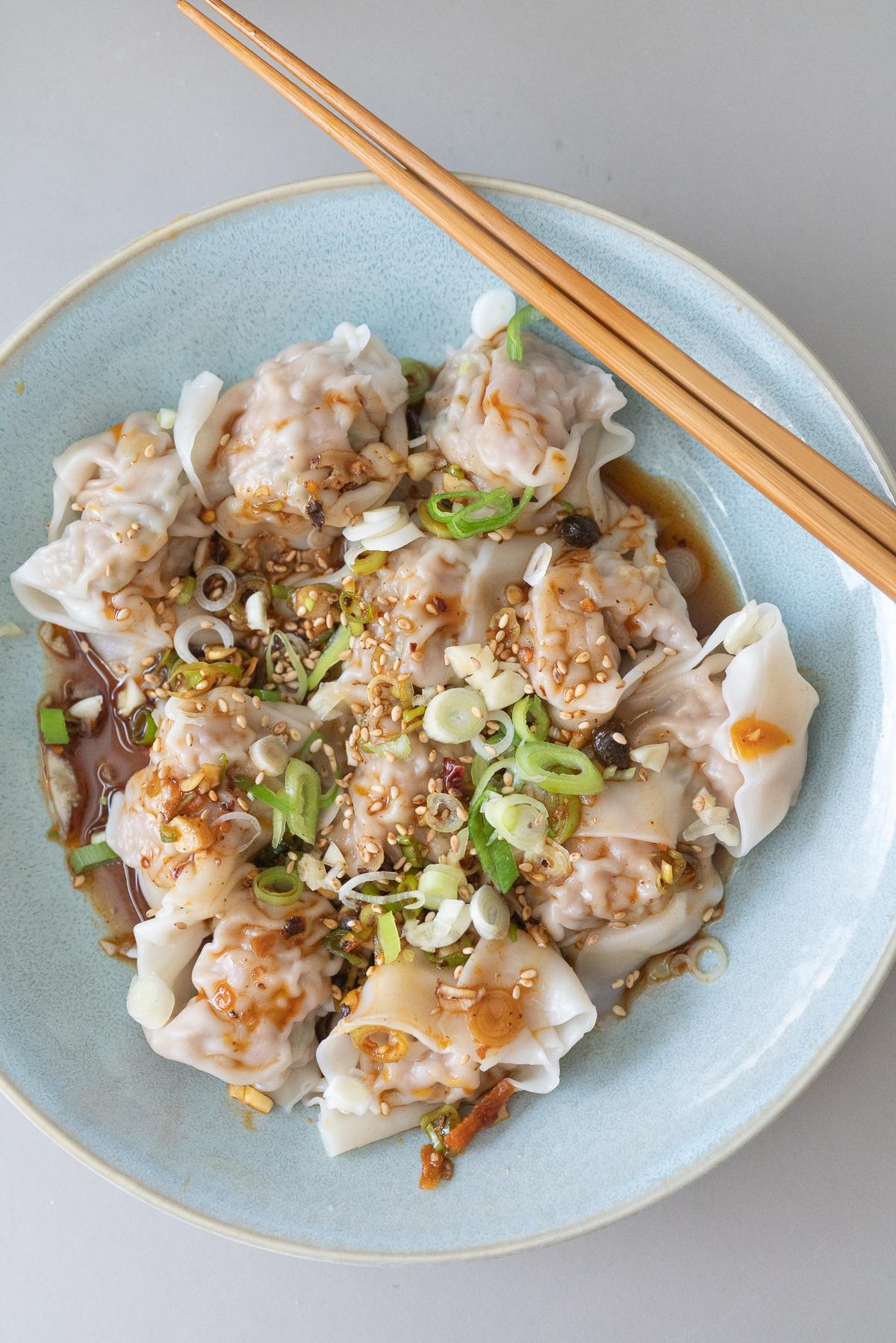 A plate of boiled wontons with wonton dipping sauce poured over