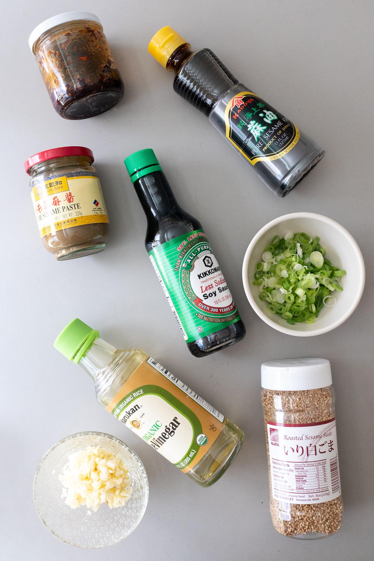 Ingredients for making Sesame Sauce (to eat with pork wontons). Soy sauce, rice vinegar, sesame oil, Chinese sesame paste, garlic, green onions, chili oil, and sesame seeds