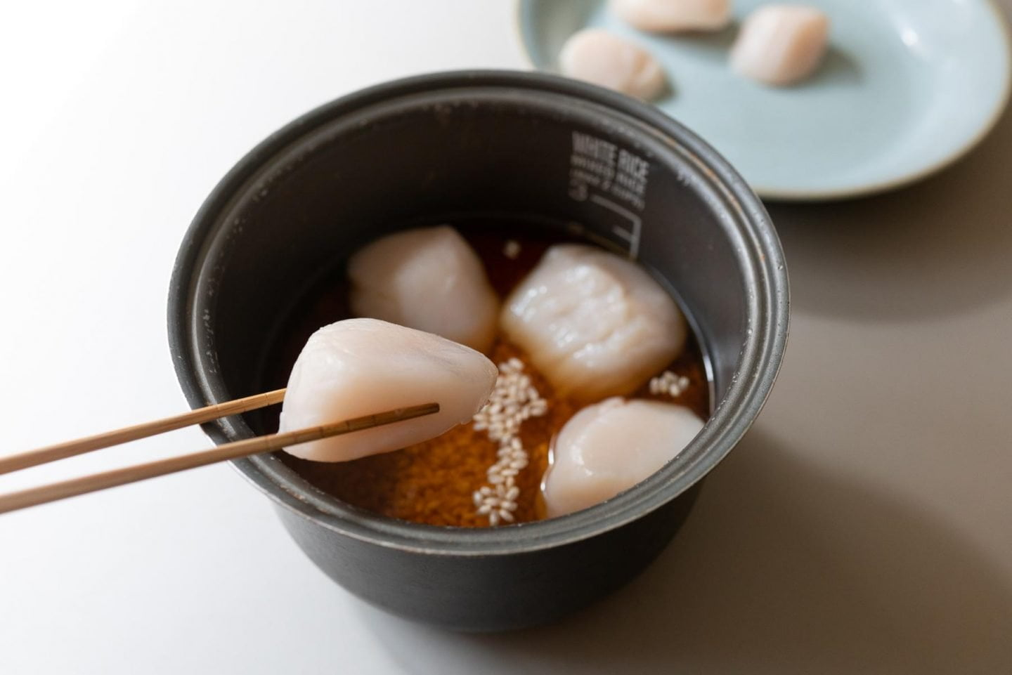 Adding raw scallops to the uncooked rice and cooking broth
