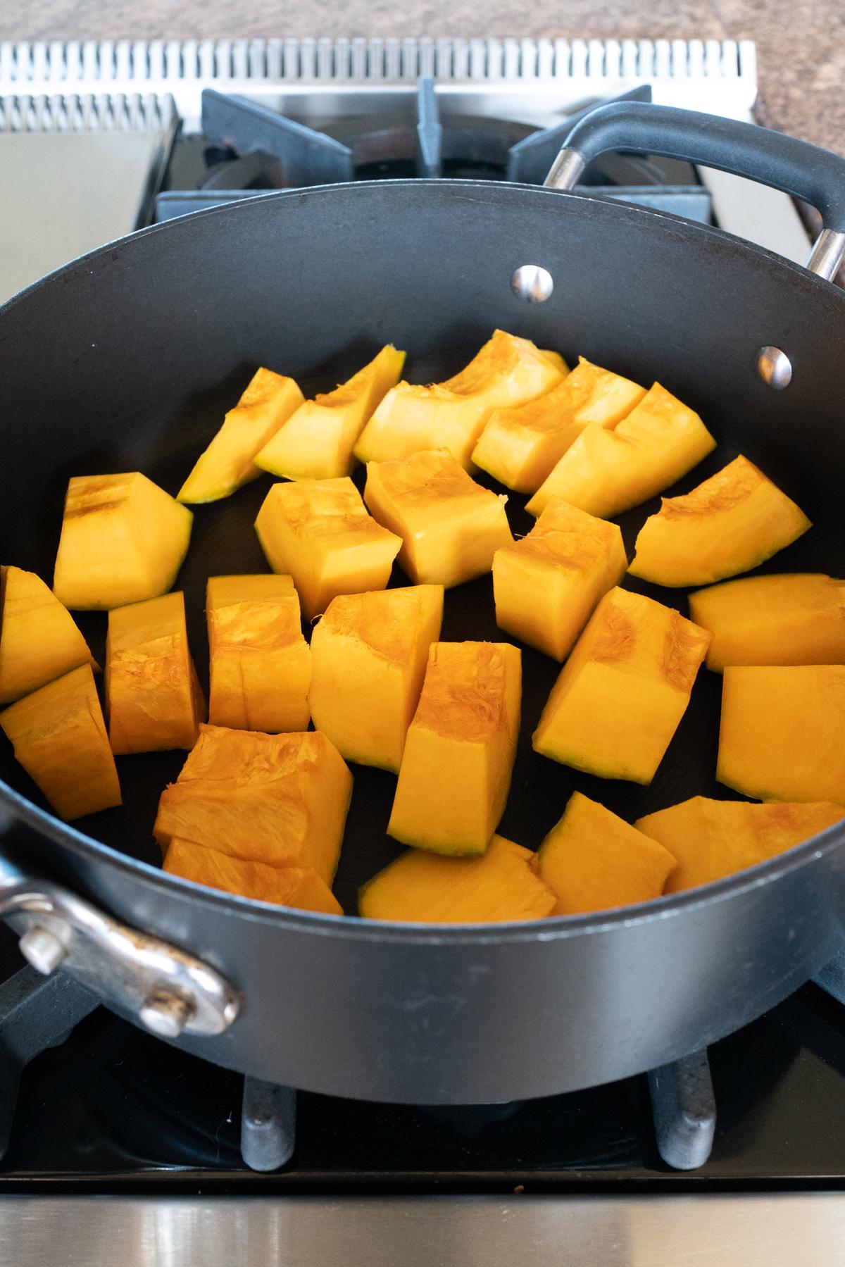 Cut kabocha squash pieces in a pan.