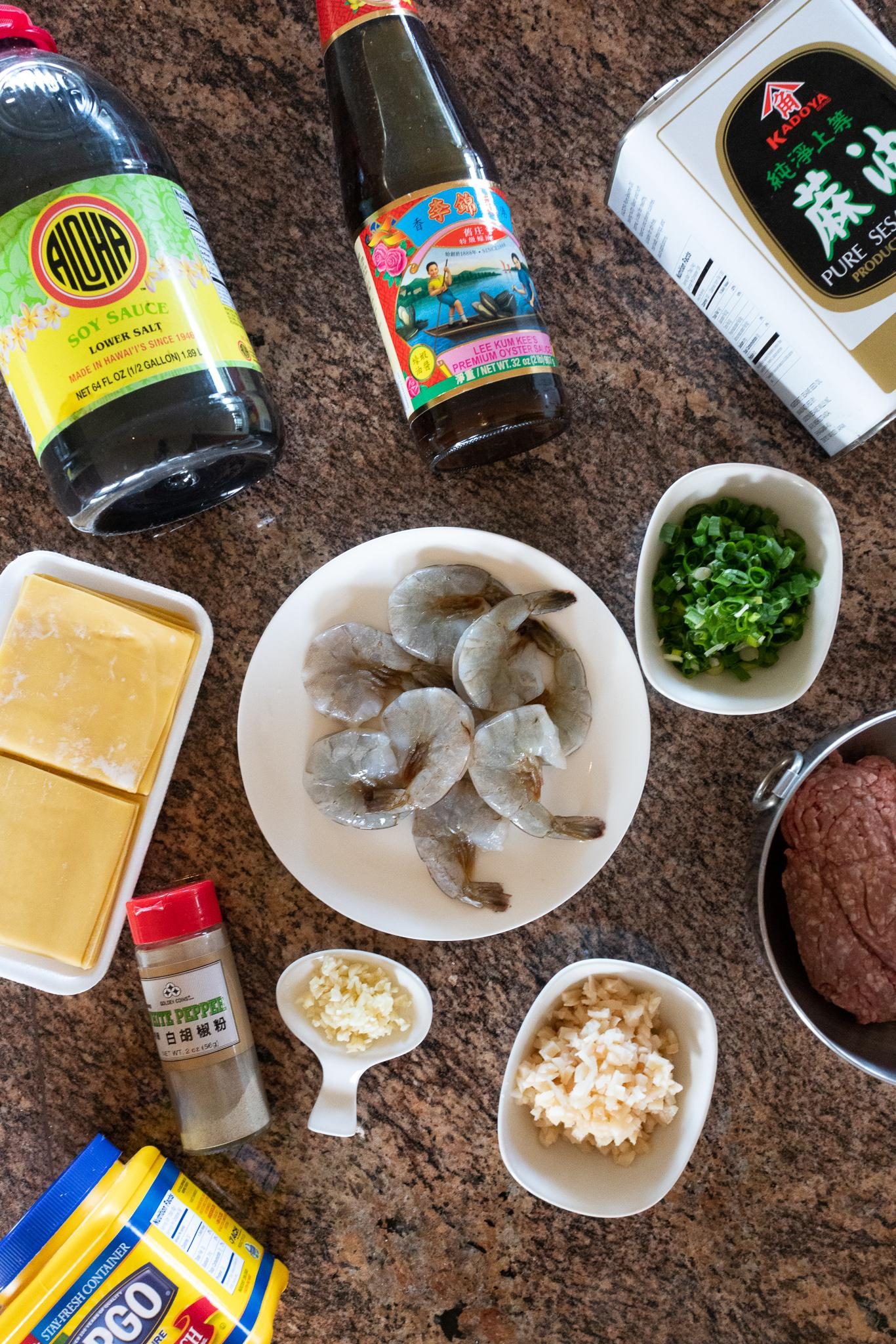 Ingredients for Gau Gee laid out: ground pork, shrimp, water chestnuts, green onions, garlic, cornstarch, soy sauce, oyster sauce, sesame oil, white pepper, and square wonton wrappers
