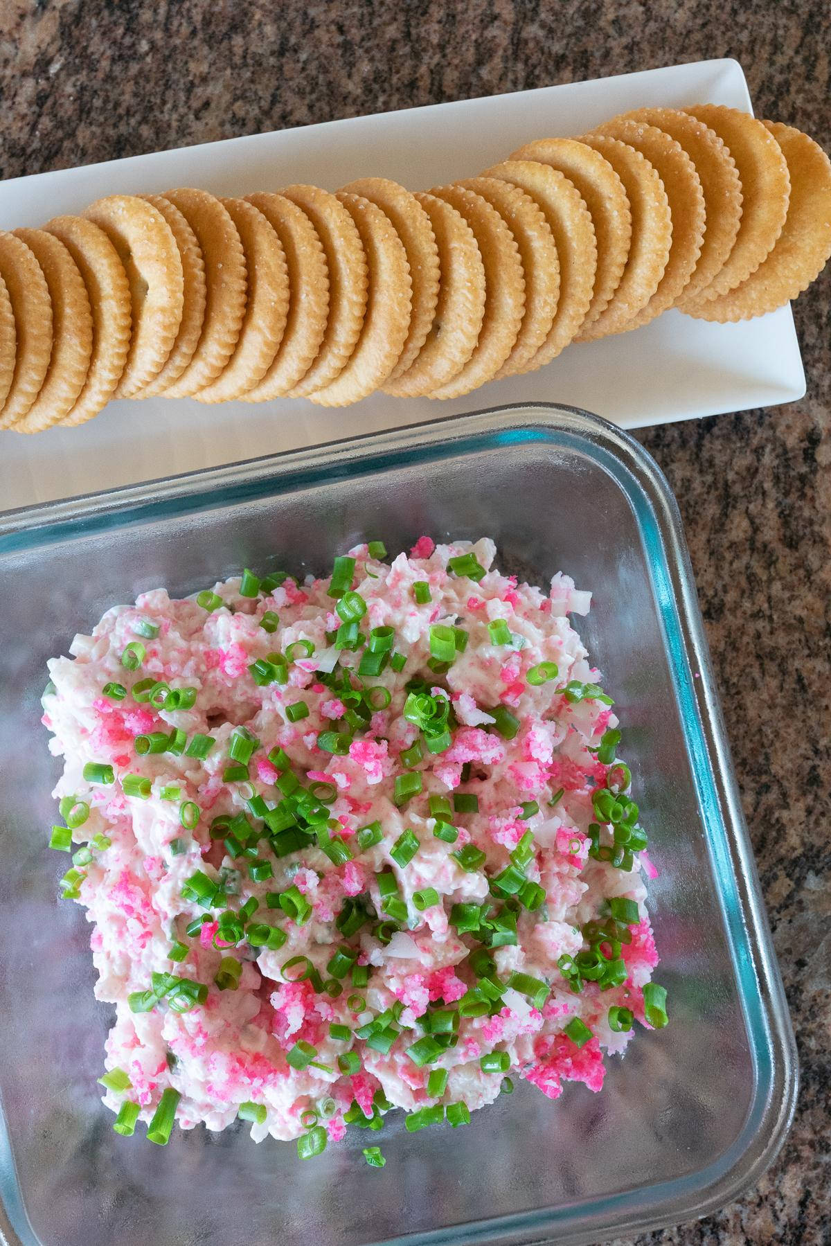 A serving dish of Kamaboko Dip and Ritz Crackers on the side.