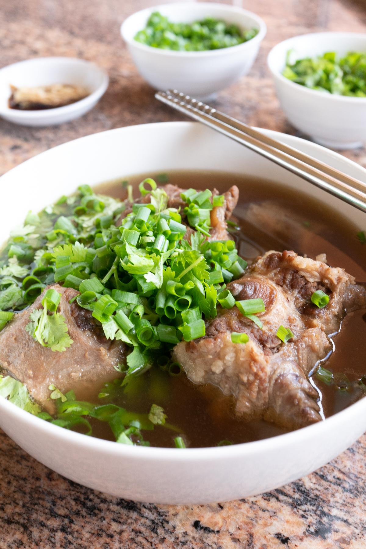 A bowl of oxtail soup with green onions and cilantro sprinkled on top.