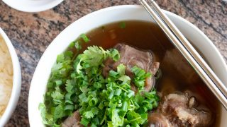 A bowl of oxtail soup with a side of rice, ginger and soy sauce for dipping, and green onions and cilantro to sprinkle on top.