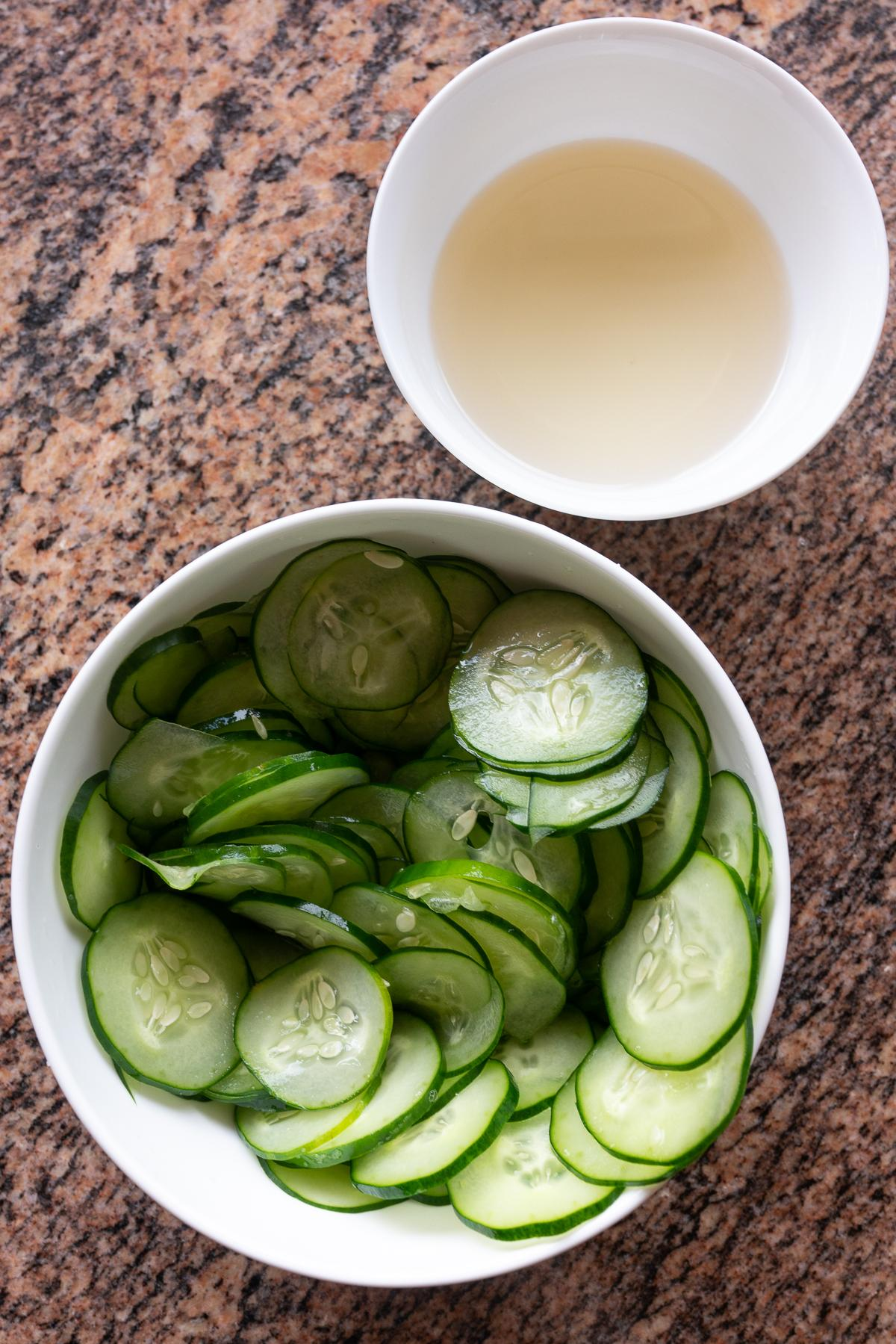 A bowl of salted, thinly sliced Japanese cucumbers. And another bowl with sugar dissolved into rice vinegar.