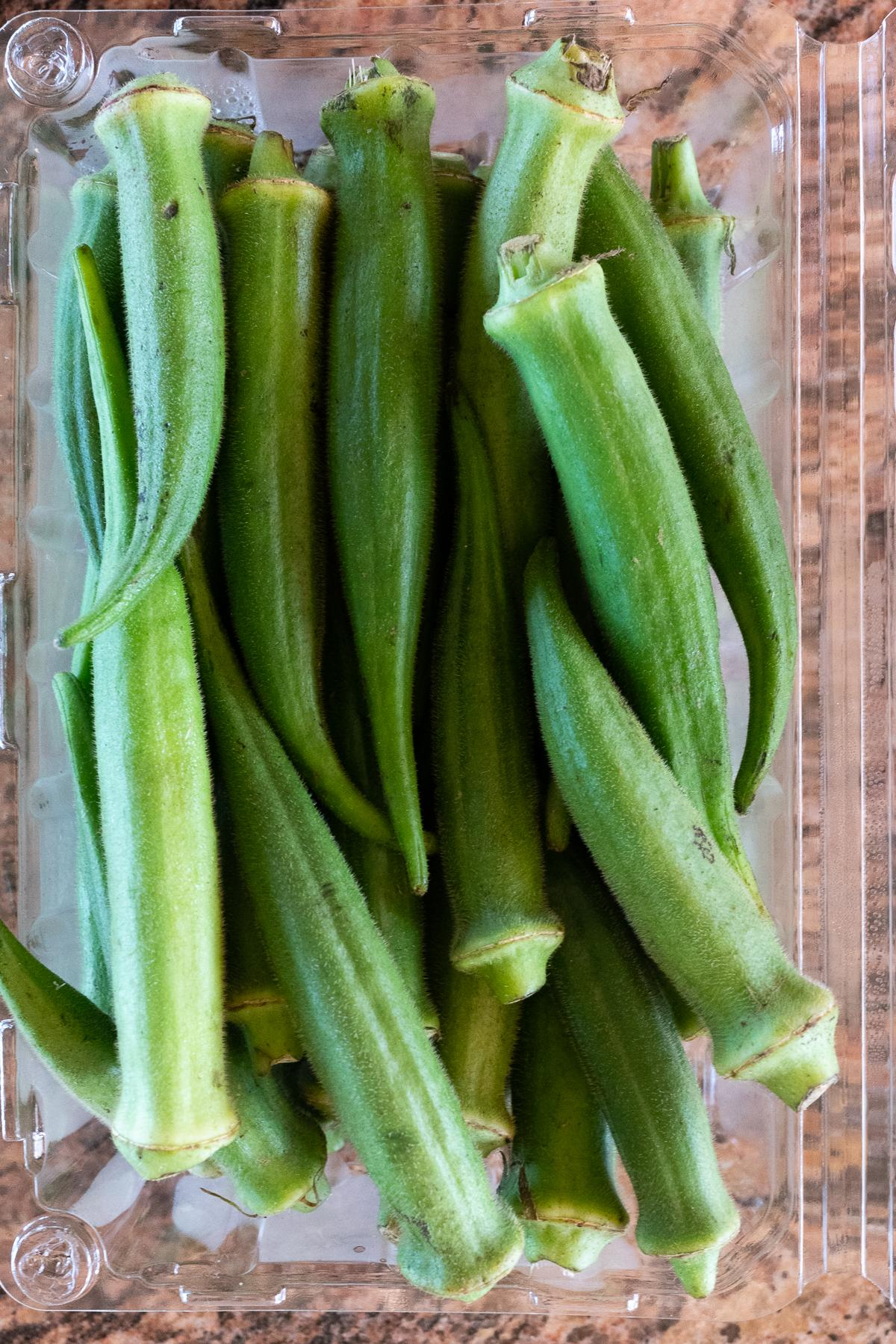 A container of fresh, raw, okra.