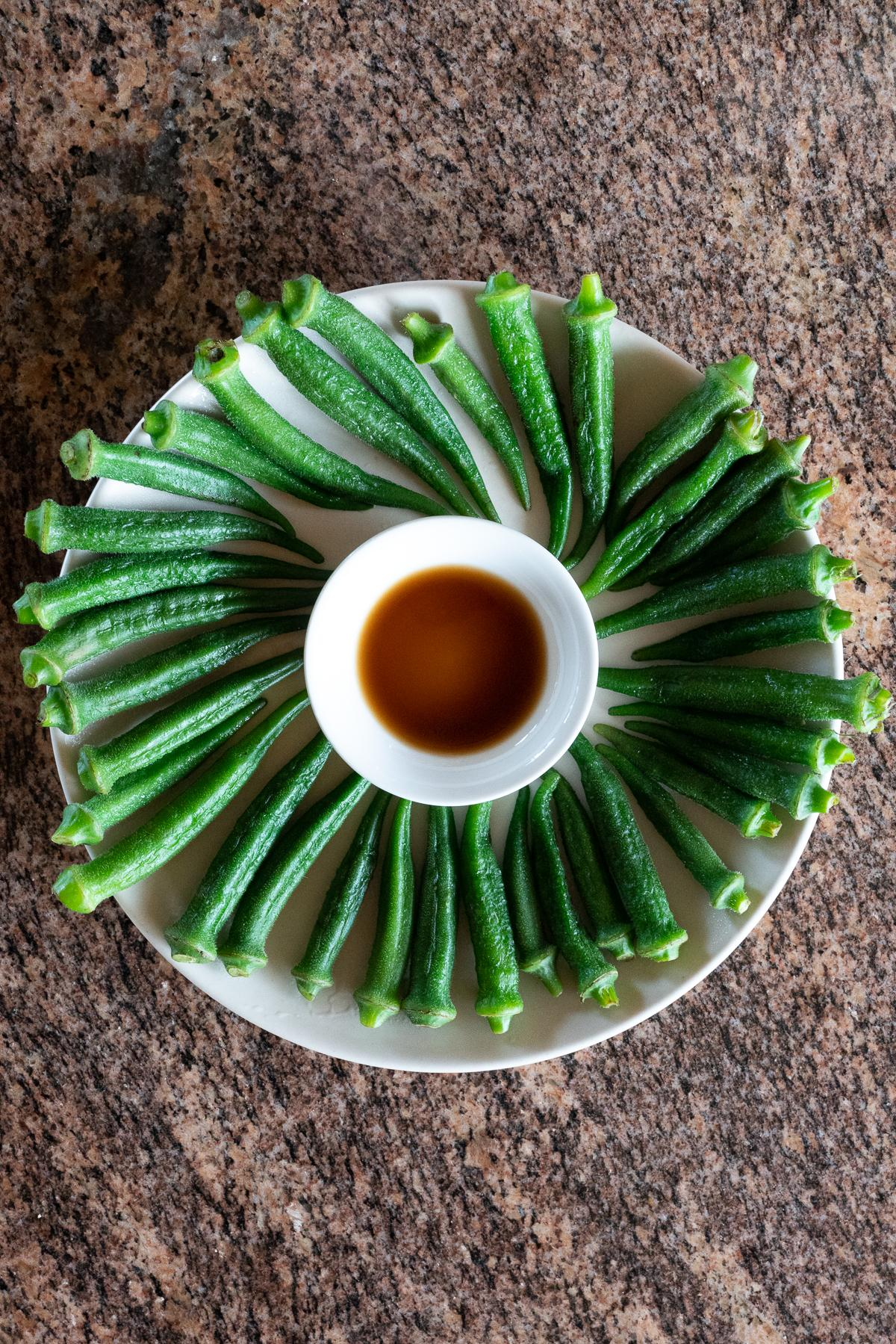 A plate of boiled okra with a small dish of soy sauce for dipping.