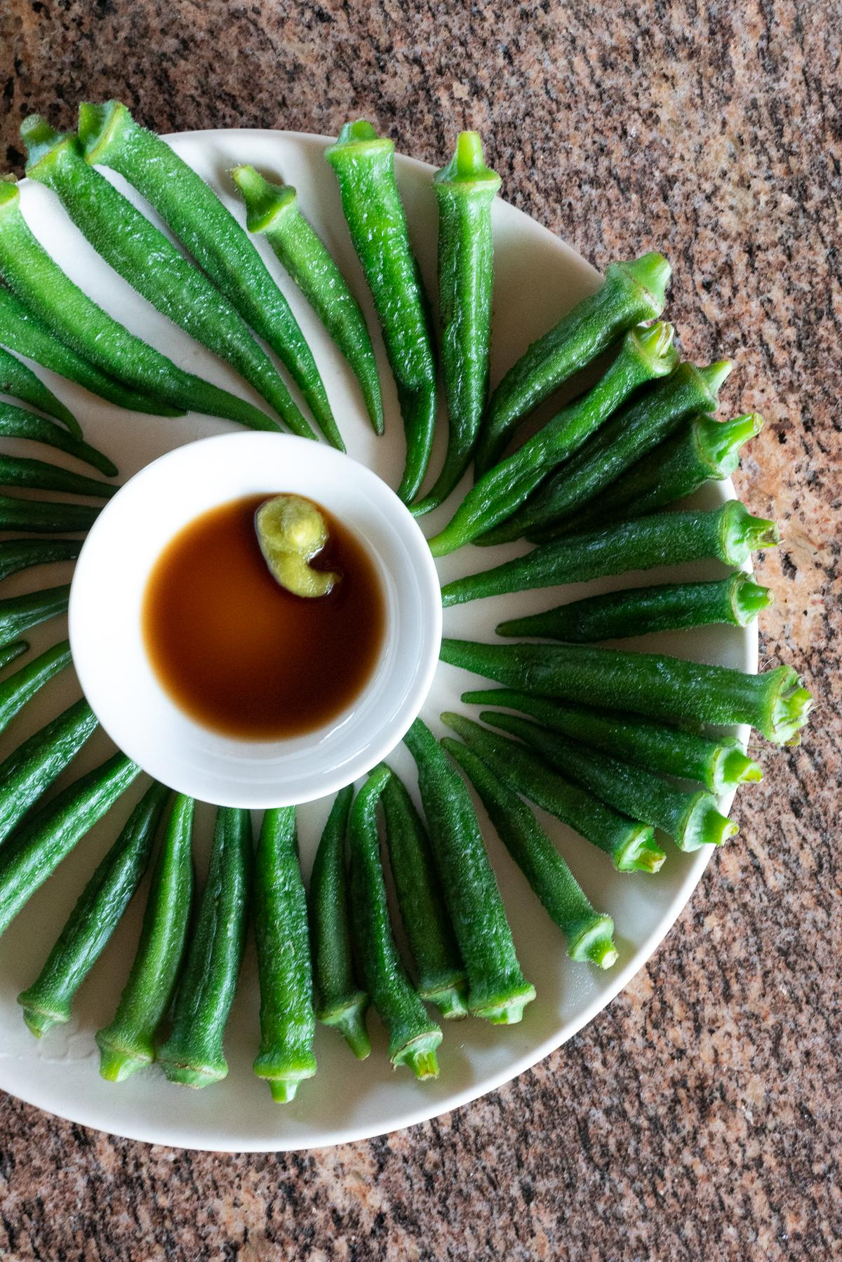 A plate of boiled okra with a small dish of soy sauce and wasabi for dipping.