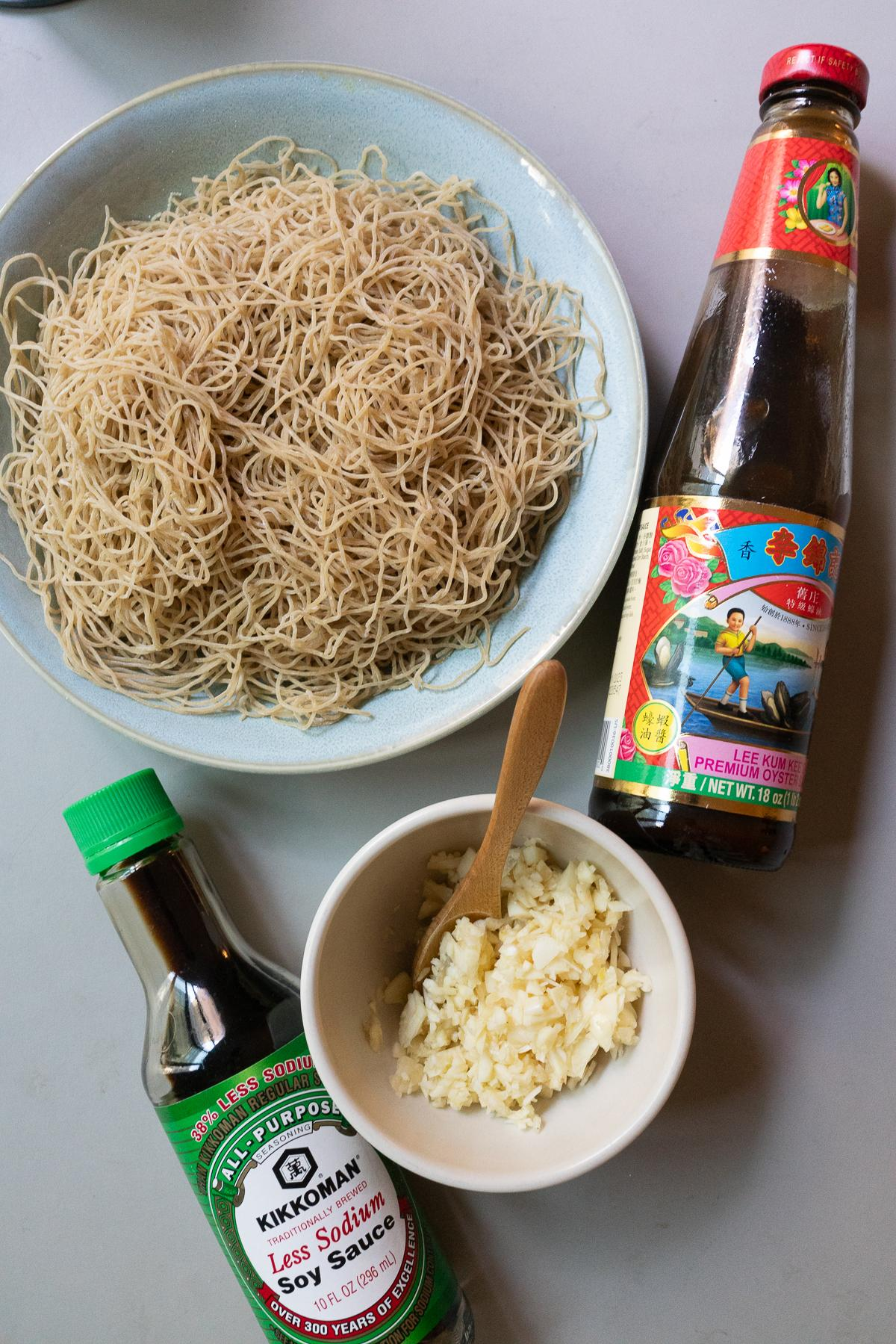 Ingredients for Gon Lo Mein: thin egg noodles, garlic, oyster sauce, and soy sauce.