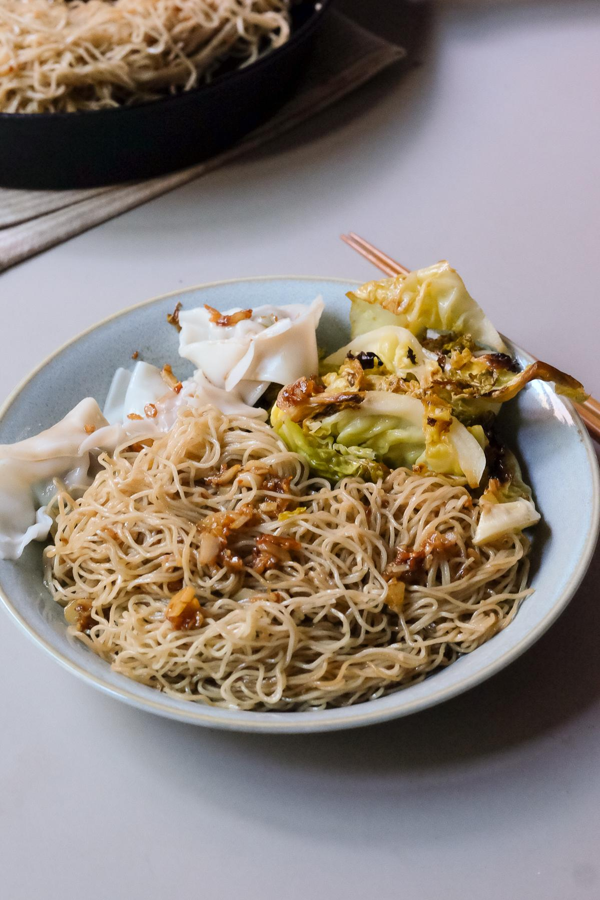 A plate of Gon Lo Mein with boiled wontons and roasted cabbage, ready to eat.