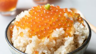 Ikura (soy sauce-cured) salmon roe over a bowl of rice with wasabi.