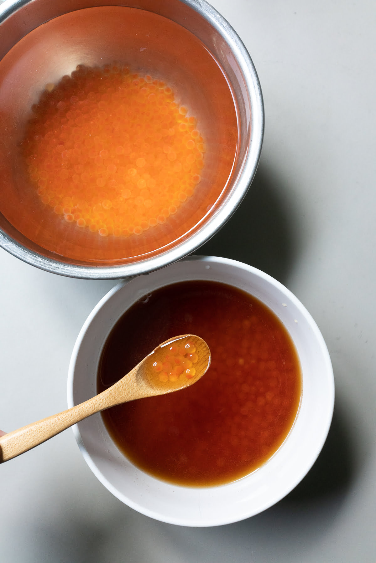 Soy sauce-cure and salt-cure poured over two bowls of cleaned salmon roe