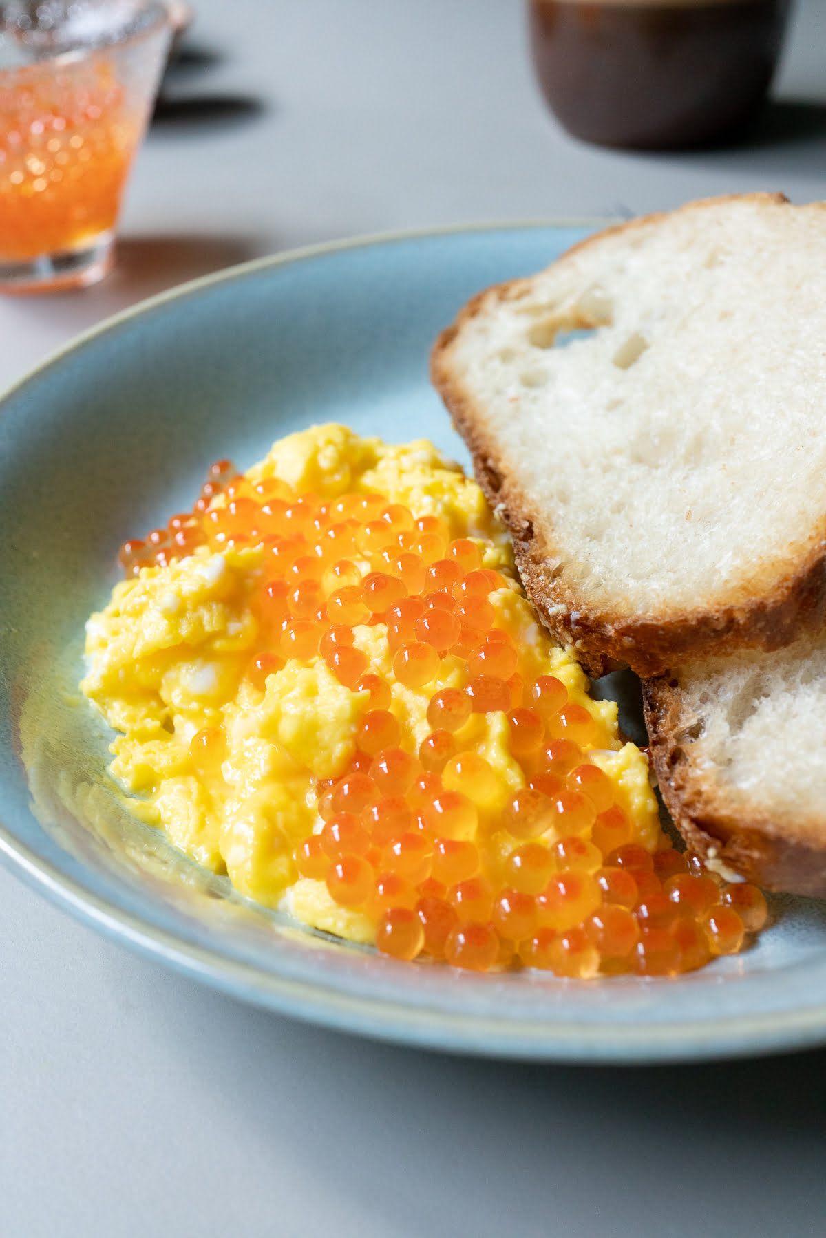 Salt-cured salmon roe over scrambled eggs with a side of toast.