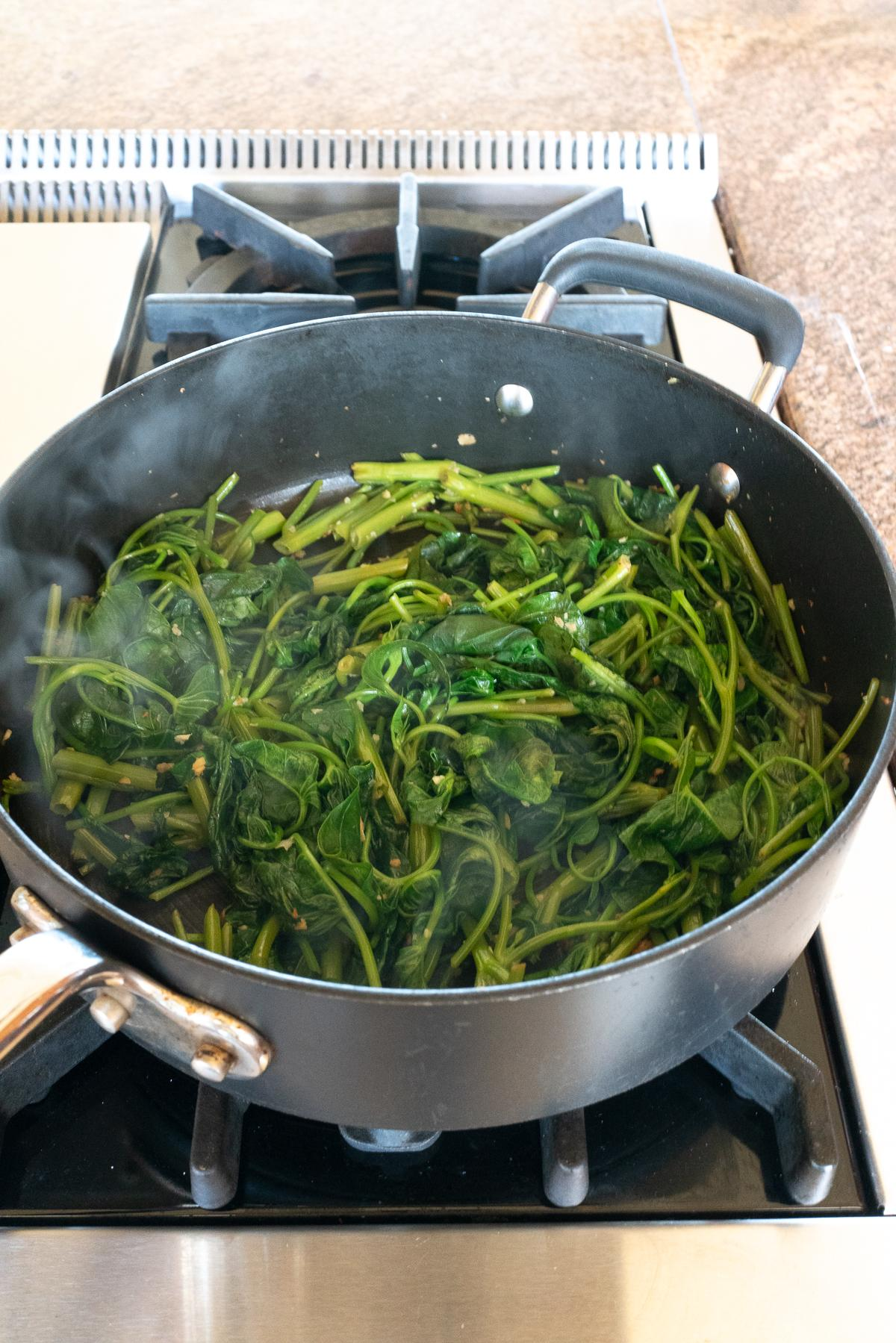 Cooking stir fried ong choy in a pan.