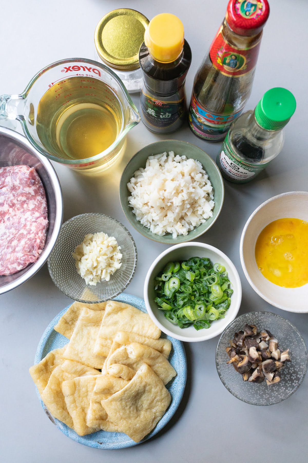 Ingredients for stuffed aburage (aburage, ground pork, garlic, water chestnuts, shiitake mushrooms, green onions, egg, soy sauce, oyster sauce, sesame oil, cornstarch, and broth), laid out on a table.