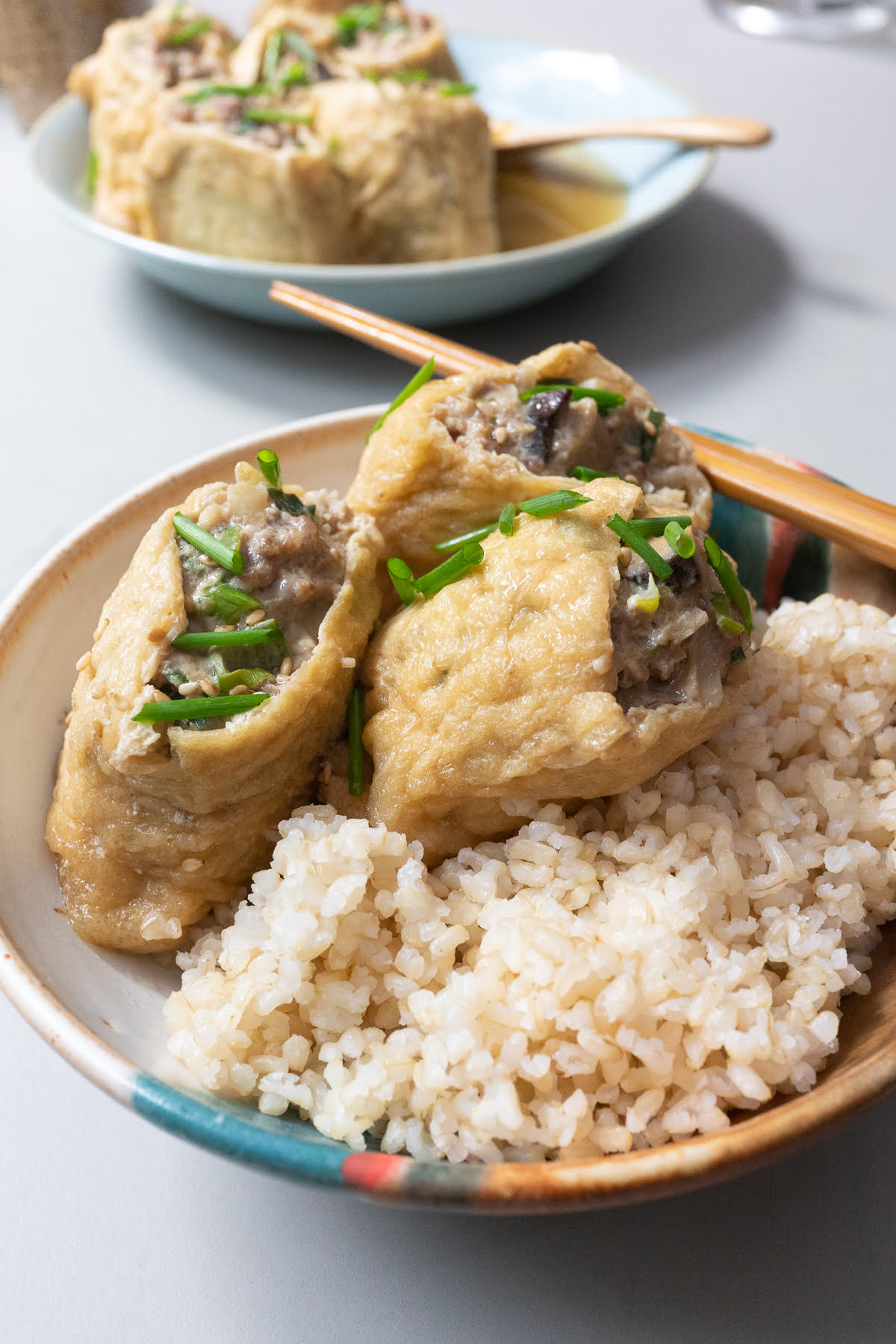Three pieces stuffed aburage served with a bowl of rice.