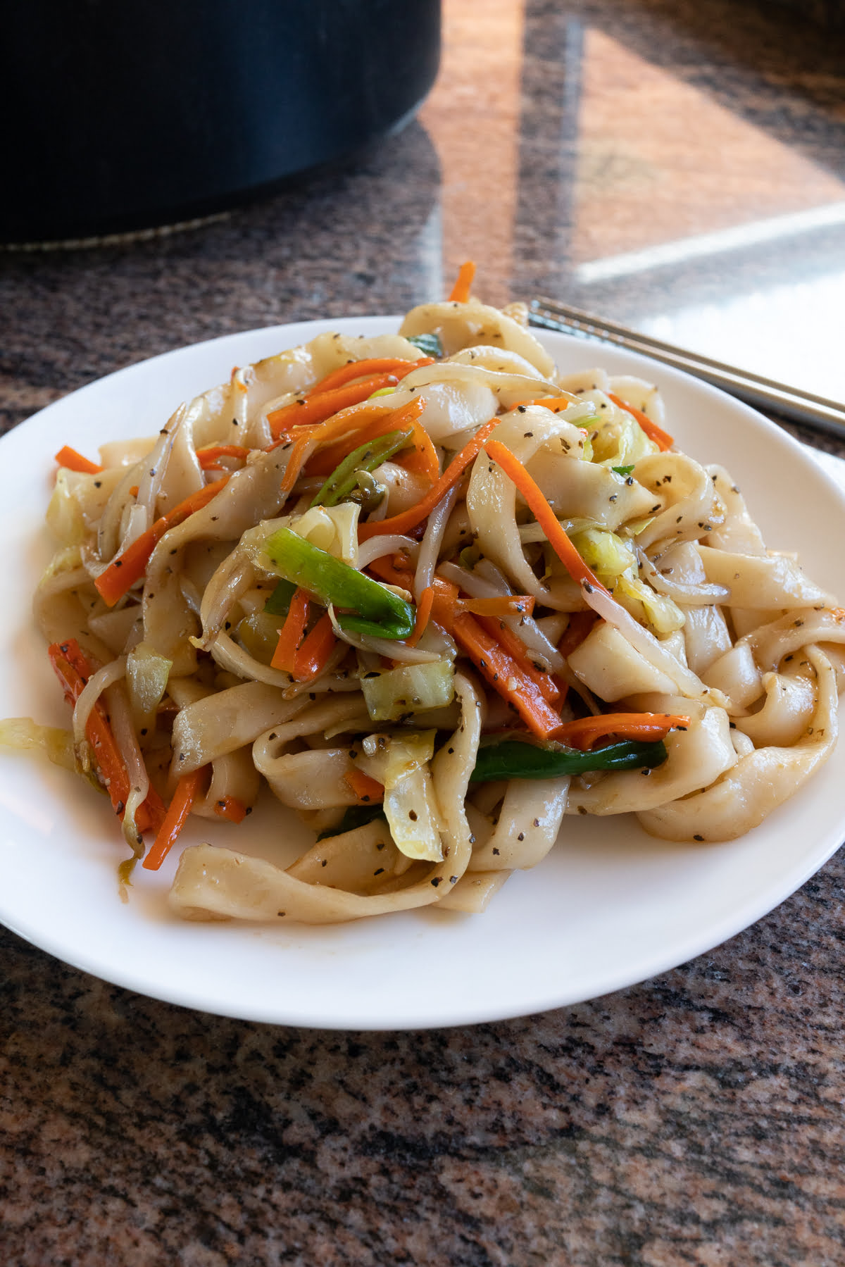 A plate of chow fun, ready to eat.