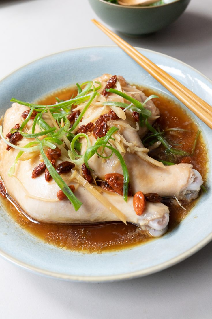 The finished dish of marinated chicken legs with ginger and goji berries, after steaming for 20 minutes. Topped with green onions for serving.