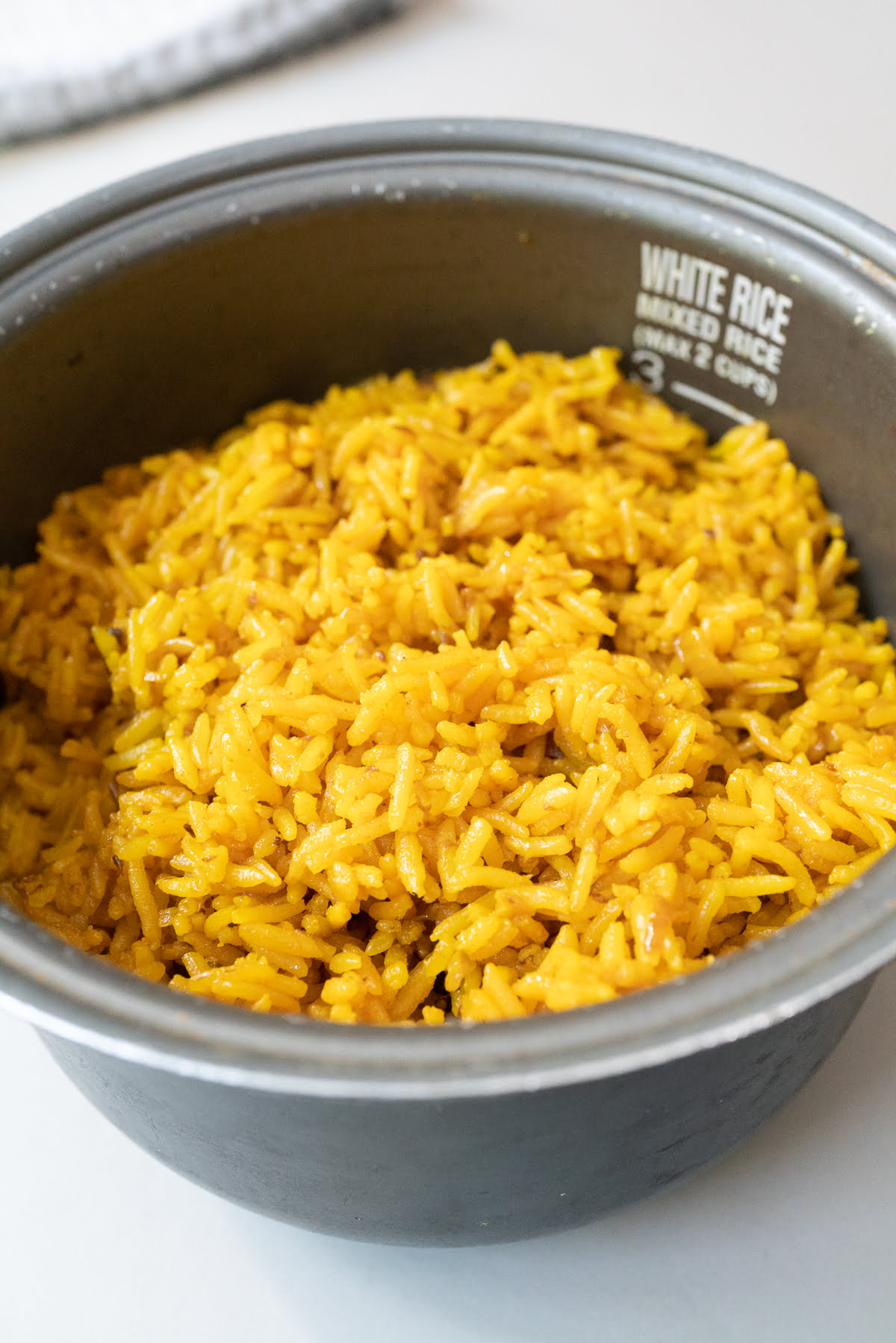 A rice cooker pot filled with freshly cooked turmeric rice.