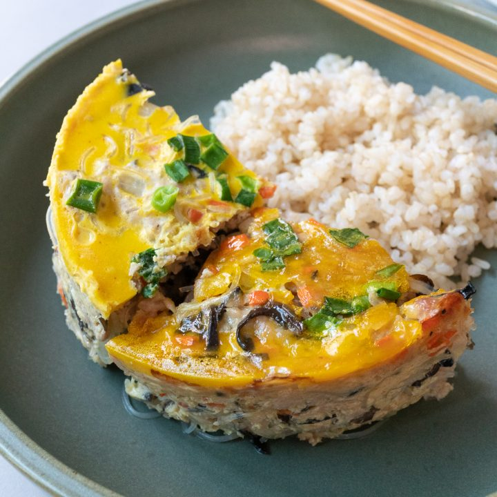 Wedges of baked and steamed Vietnamese Egg Meatloaf (Cha Trung) served with rice.