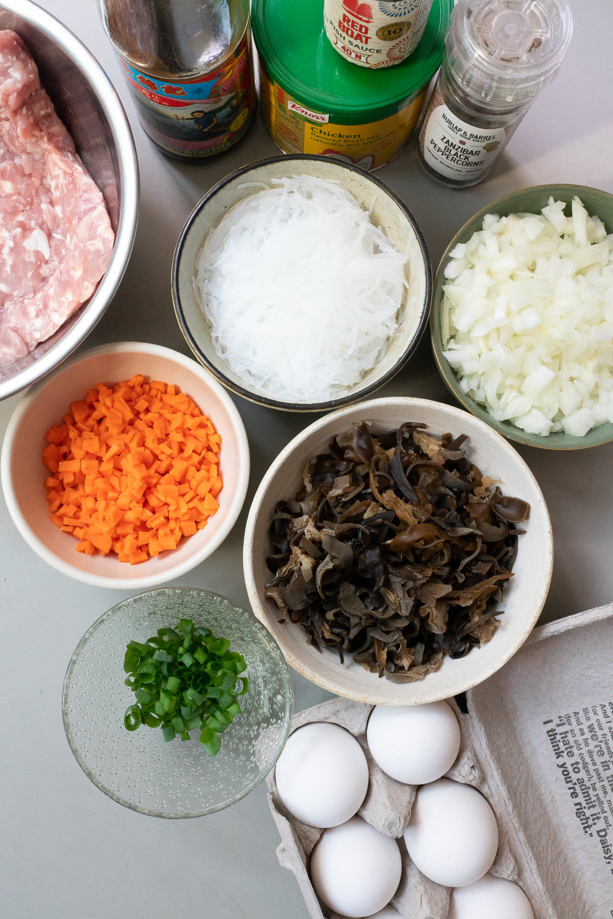 Ingredients for Vietnamese Egg Meatloaf (Cha Trung): ground pork, mung bean noodles, wood ear mushrooms, eggs, carrots, onions, green onions, fish sauce, oyster sauce, chicken bouillon powder, and black pepper.