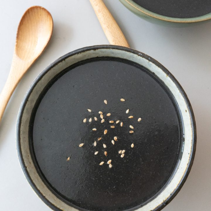 Bowl of Black Sesame Soup, topped with white sesame seeds.