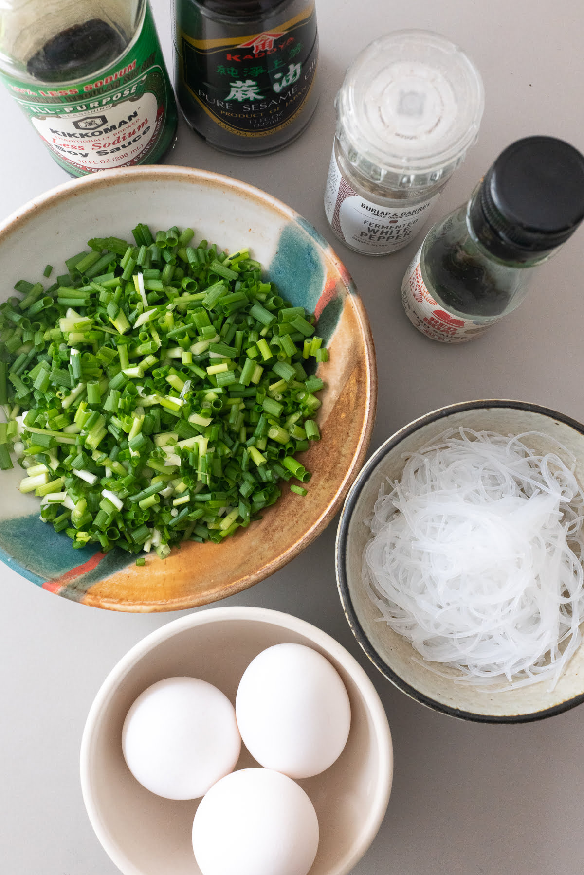 Ingredients for Chive Vermicelli Egg Pancakes laid out on a table. Featuring chives, eggs, vermicelli noodles, soy sauce, fish sauce, sesame oil, and white pepper.