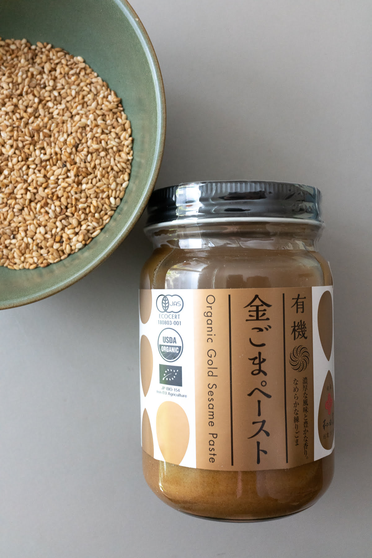 A jar of white sesame paste and a bowl of roasted white sesame seeds.