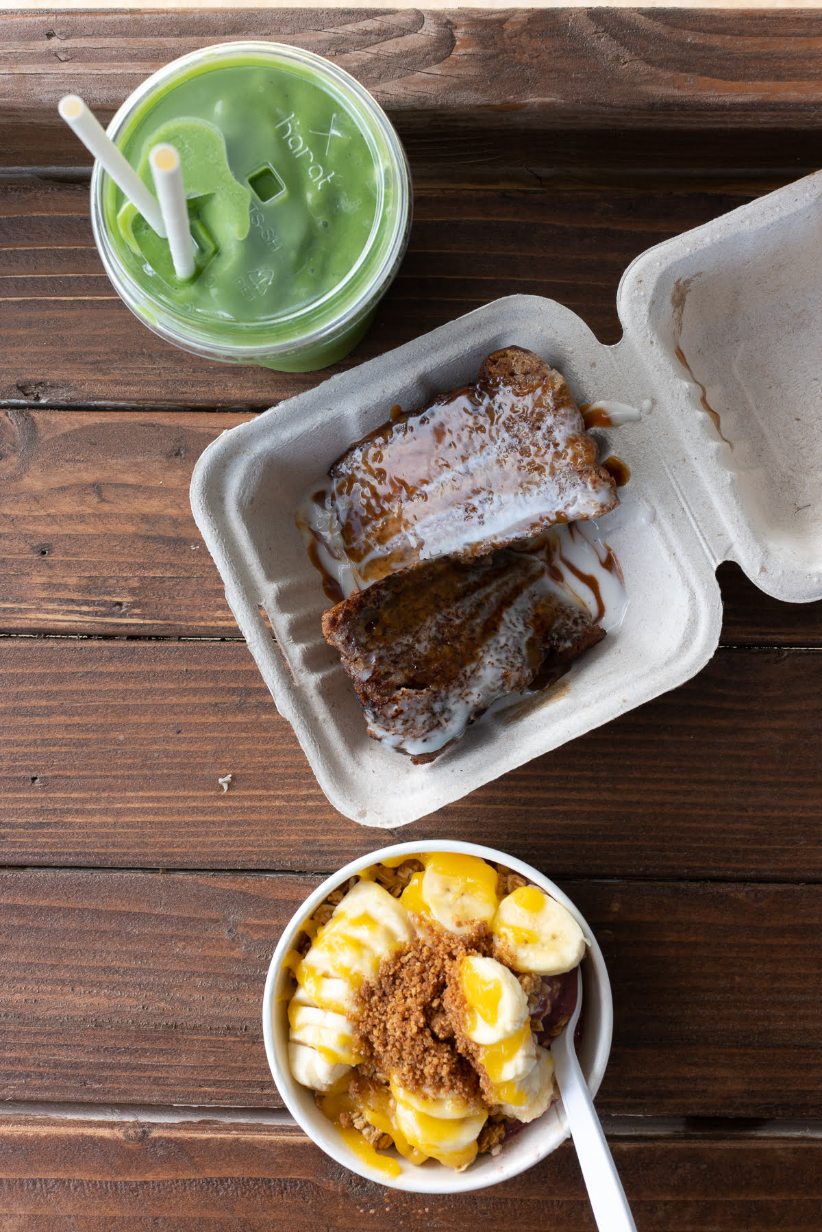 Overhead shot of açaí bowl, grilled banana bread, and green smoothie from Kahuku Farms.