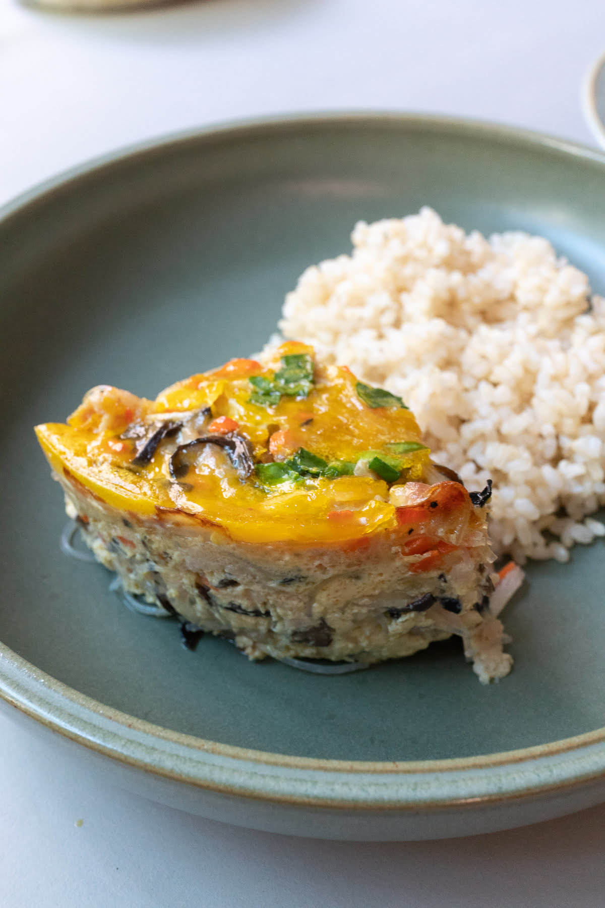 Wedge of baked Vietnamese Egg Meatloaf (Cha Trung) served with rice.