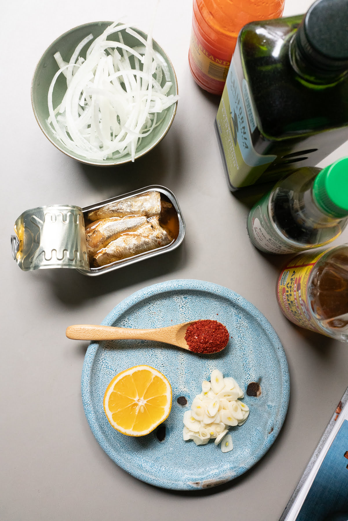 Ingredients for Sardine Pupu: canned sardines, onions, garlic, Korean chili pepper, lemon, olive oil, soy sauce, apple cider vinegar, and chili pepper water.