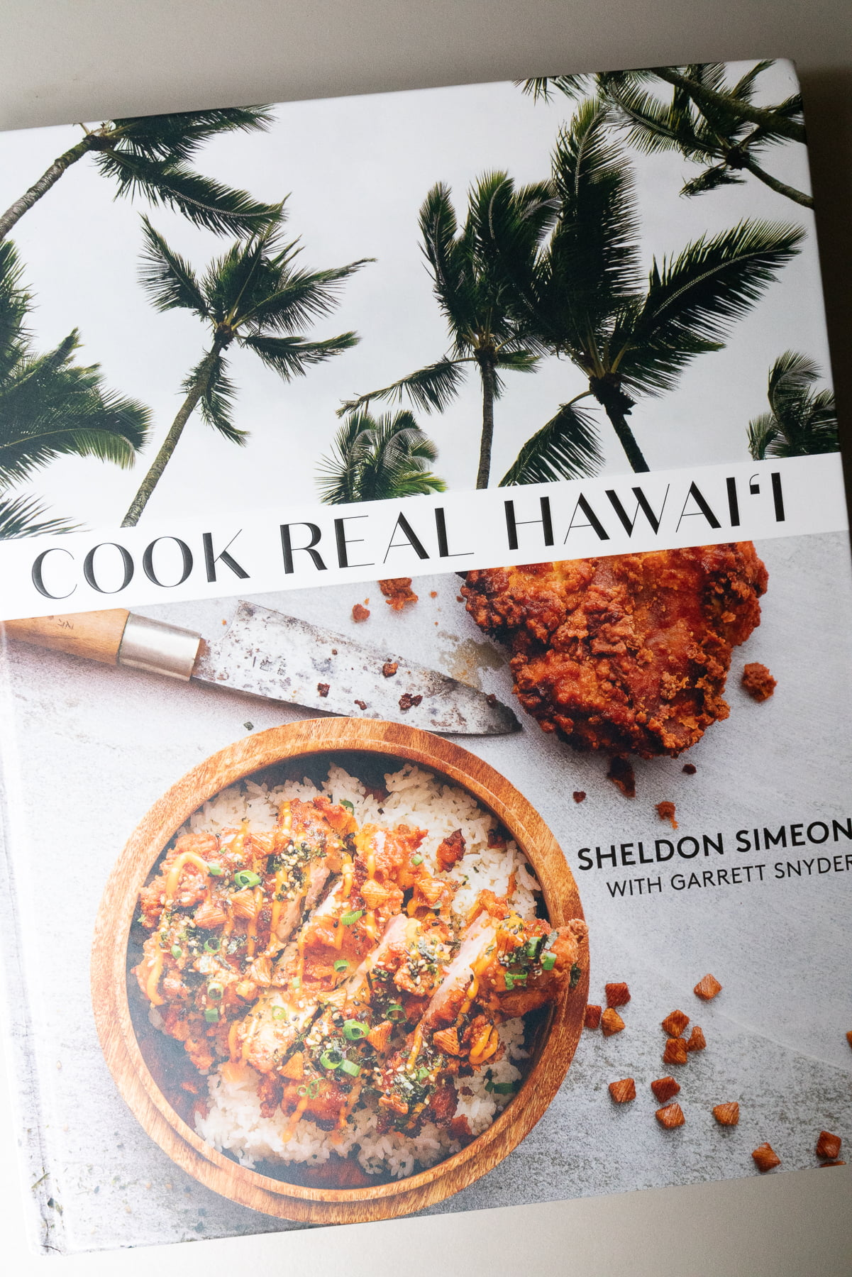 Book cover of Cook Real Hawaii by Sheldon Simeon and Garrett Snyder.