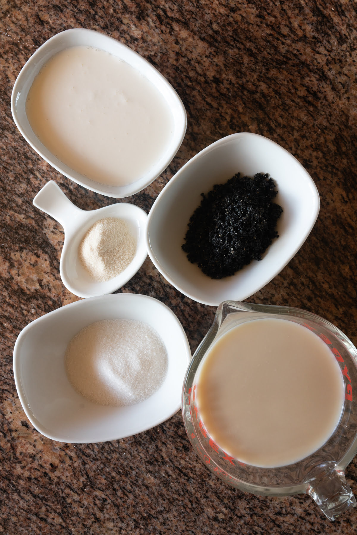 Ingredients for black sesame pudding laid out on the counter (black sesame paste, heavy whipping cream, sugar, agar agar powder, whole milk (or soy milk), and sugar.