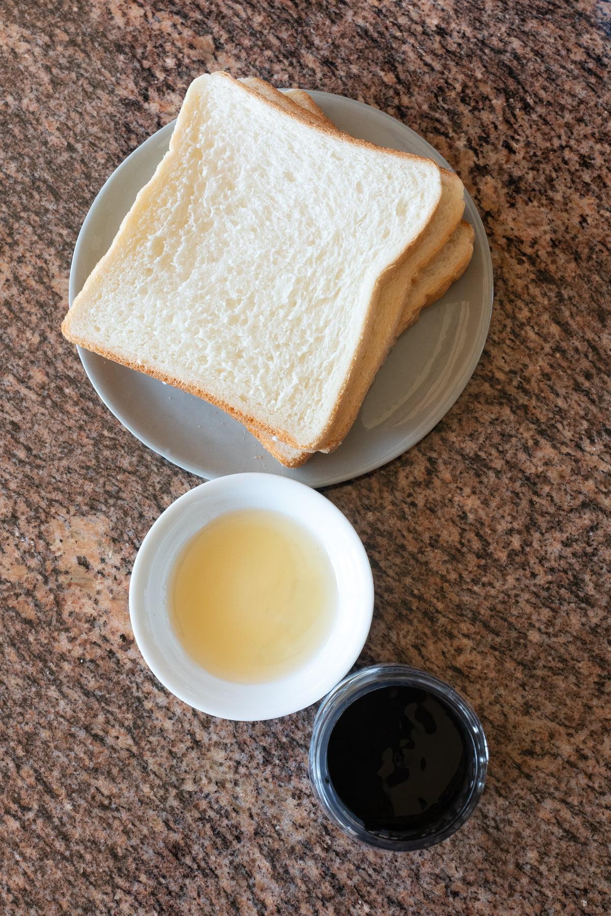 Ingredients for Black Sesame Toast (soft white bread, honey, and black sesame paste).