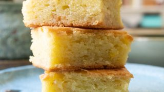 A stack of butter mochi squares on a plate.