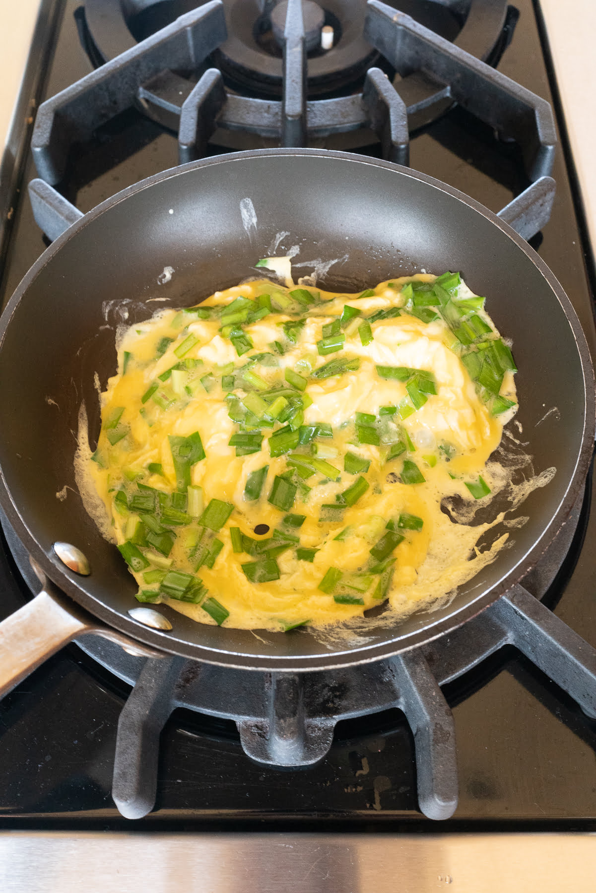 Scrambling together the chive and eggs in a pan.