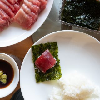 Homemade sushi on a plate with. Plates of ahi sashimi, soy sauce and wasabi, and seaweed on a table.