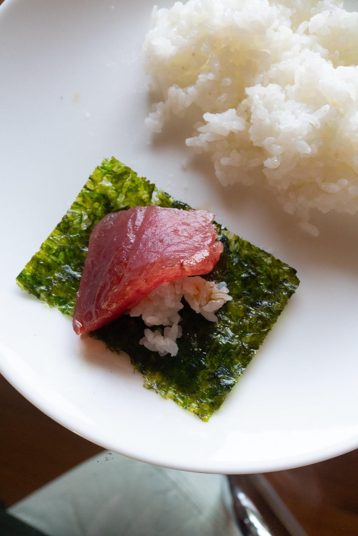 A piece of seaweed topped with sushi rice and ahi sashimi to make homemade sushi.